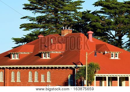 Historic brick building surrounded by large Cypress Pine Trees taken at the Presidio in San Francisco, CA