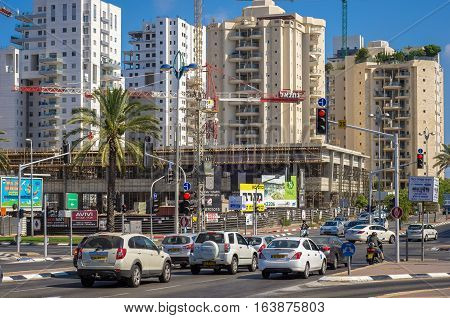 Holon Israel-July 21 2016: Two-story modern commercial complex BeSdera is constructed in city center on multi-story residential apartment buildings background. Cars wait traffic light in foreground
