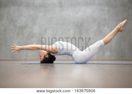 Side view portrait of beautiful young woman wearing white sportswear working out in fitness center against grey wall, doing yoga or pilates exercise. Variation of Matsyasana, Fish pose. Full length