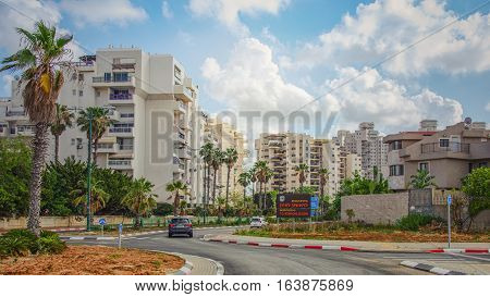 Rishon LeZion Israel-May 27 2016: The entrance to Rishon LeZion from Bat Yam by Menachem Begin Road. Two small cars enter the city to Heil HaTothanim Street along multi-story residential buildings
