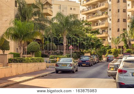 Holon Israel-July 21 2016: Little quiet Yigael Yadin Street is flooded with morning sunlight. There are modern residential apartment buildings green palm trees parked cars along sidewalk. Wide shot.