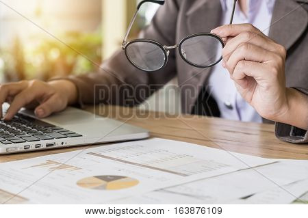 close up business women hand holding spectacles with using laptop computer and stock maket document on wood desk. release concept. selective focus.