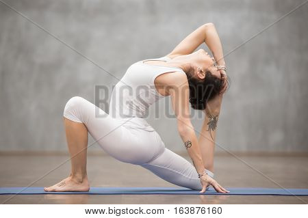 Side view portrait of beautiful young woman with tattoo on her foot meaning Wild kitty working out in fitness club or at home, doing yoga, pilates exercise. Variation of low lunge, anjaneyasana pose