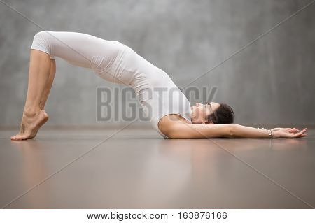 Side view portrait of beautiful young woman with tattoo on foot meaning Wild cat working out in fitness club or at home, doing yoga, pilates exercise. Variation of shoulder bridge pose. Full length