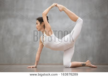 Side view portrait of attractive young woman with beautiful tattoo working out against grey wall, doing yoga, pilates balancing exercise. Sunbird, chakravakasana pose. Full length