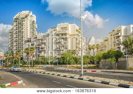 Rishon LeZion Israel-May 27 2016: White multi-story residential buildings are flooded with warm early sunset light. The apartments are located in Neve Hof neighborhood closed to city entrance from Bat Yam. Wide shot on blue sky background