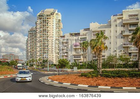 Rishon LeZion, Israel-May 27, 2016:  Roundabout with young palm trees on Menachem Begin Road. There are white multi-story residential apartment buildings in blue sky background. White taxi car rides in foreground