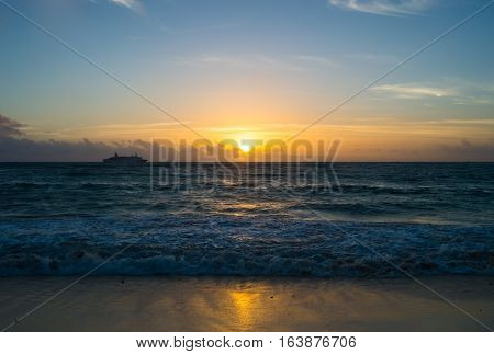 Sunrise at Playa del Carmen beach with ship on the horizon