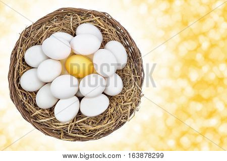 Top view of Golden egg standing out from white eggs on nest in wicker basket with concept of uniqueness different and on yellow bokeh background and include path copy space