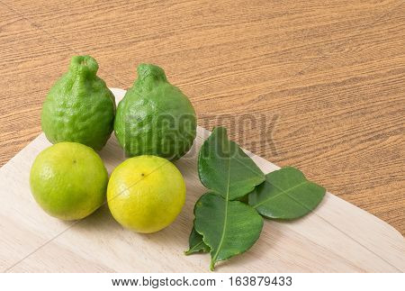 Vegetable and Herb Fresh Green Kaffir Lime with Persian Lime and Kaffir Leaves for Seasoning in Cooking on A Wooden Board with Copy Space For Text Decorated.
