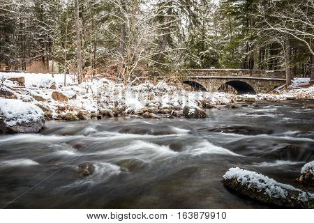 Winter river scene in the snowy forest and double arch stone bridge in background