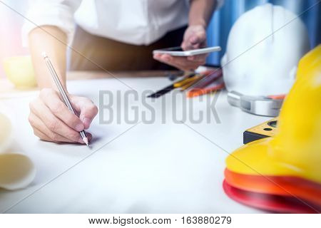 Close Up Hands Of Engineer Start-up Drawing Plan Or Blueprints Together At Desk, Holding A Mobile Ph