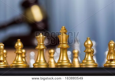 Close Up Golden King Of Chess Or Checkers With Blurry Gavel Meaning Fighting, Justice And Victory Fo