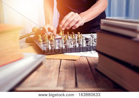 Close Up Young Lawyer Businessman Playing Chess In Corthouse, Vintage Tone With Sunlight Effect Phot