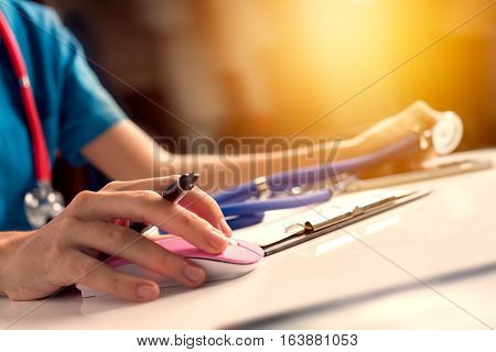 Close Up Asian Woman Doctor Working In Hospital Using Computer Mouse And Holding Stethoscope To Chec