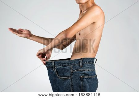 Asian Young Male Thin Body In Big Jeans Measuring With Hand Palm Up In Studio Shot Photography.