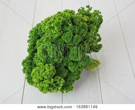fresh green curly parsley on white wooden background
