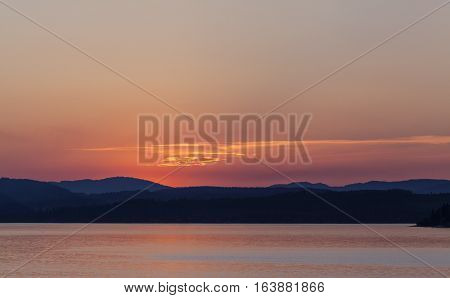 Nordic night and Nordic light during June, July and August. Sea or lake and the coastline, hills and ridges.