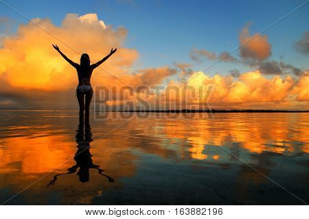 Silhouetted Woman Standing In A Water At Sunset On Taveuni Island, Fij
