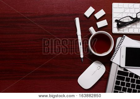 Creative office stuff top view business equipment and it technology display on dark grunge wooden table for vintage style of background with copy space.