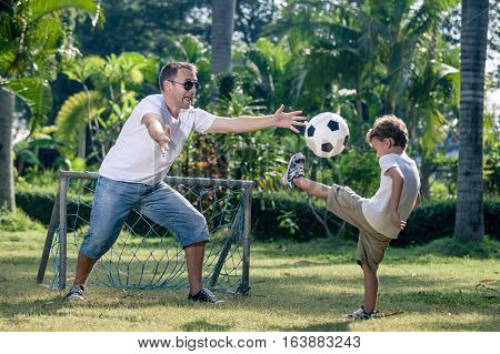 Father And Son Playing In The Park At The Day Time.
