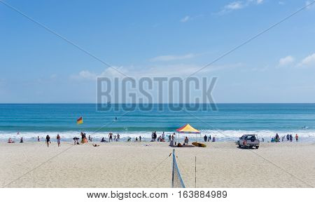 Mount Maunganui, New Zealand - December 21, 2016; ocean beach with beach volleyball net and people enjoying summer and beach activities between the flags and lifesavers shelter.