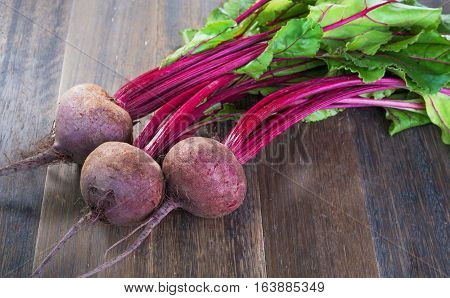 Fresh whole beetroots with leaves on wooden rustic table.Whole beetroots