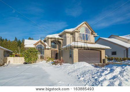 Big luxury house with front yard in snow. Residential house on winter sunny day