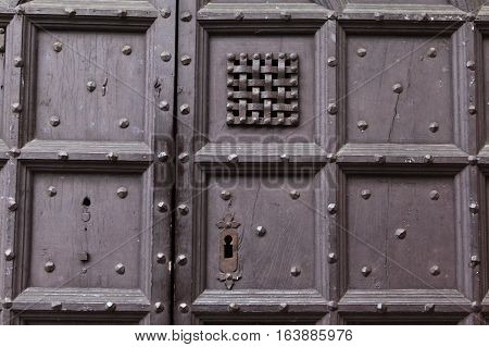 Background: fragment of a wooden door - boards painted in a dark blue cap and forged iron nails, keyhole and window with bars. Style Medieval Europe (France).