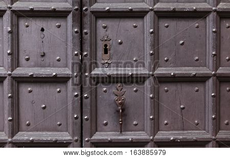 Background: fragment of a wooden door - boards painted in a dark blue cap and forged iron nails, door handle, keyhole and window with bars. Style Medieval Europe (France).