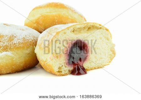 Close up of a cut jam filled doughnut on a white background