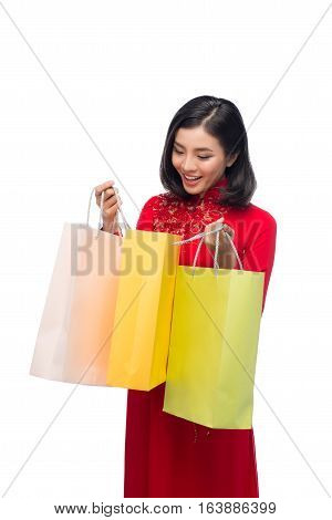 Portrait of a beautiful Asian woman on traditional festival costume Ao Dai holding shopping bags.