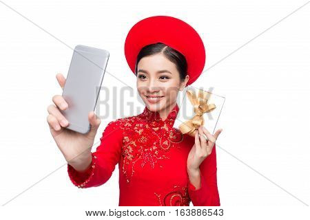Portrait of a beautiful Asian woman on traditional festival costume Ao Dai holding Gift Box taking selfie photo by smartphone