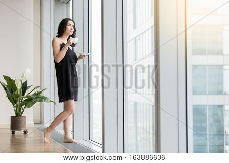 Full length view of young woman standing near window enjoying coffee, looking at city after waking up at morning, wearing black silk nightwear, resting from the business, waiting for good weather