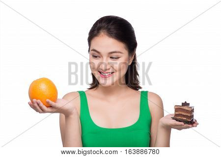 Diet. Dieting concept. Healthy Food. Beautiful Young Asian Woman choosing between Fruits and Sweets
