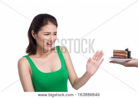 Diet and nutrition concept. Beautiful young asian woman afraid cake isolated on white.