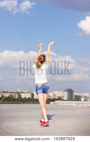 Young slim beautiful girl dancing on the roof of the house warm sunny summer day against the blue sky with clouds. Happy summer