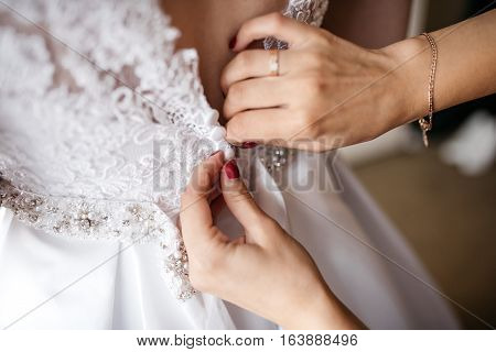 The bride wears a wedding dress. Closeup, back in a corset and human hands