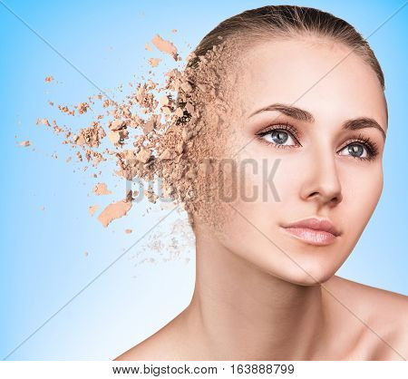 Woman face made from crumbly powderover blue background