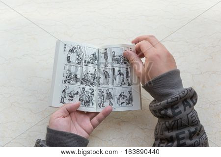 ZhongShan China-January 4:man reading a book named Old Master Q on January 4 2017.Old Master Q is a popular Hong Kong comic created by Alfonso Wong and appeared in 1962 and serialised in 1964.
