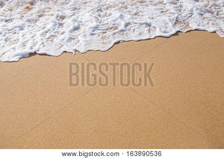 foam wave on the sand beach background.
