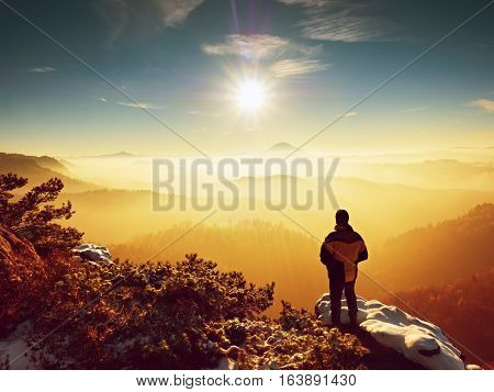 Tall hiker in black on rocky peak watch the world . Heavy orange mist bellow in valley. Wonderful breathtaking daybreak in mountains.