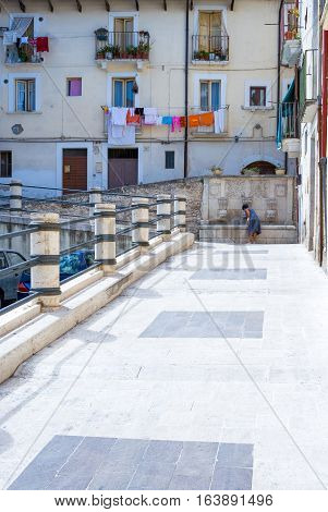 Sulmona Italy - September 8 2006: A woman fetching water from an ancient fountain in the old town centre