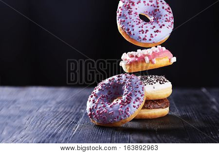 Donut with pink icing and marshmallow in motion falling on a tasty donuts with blue, chocolate and vanilla icing on a dark wooden background.
