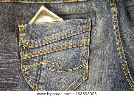 Condom in the pocket of the blue jeans