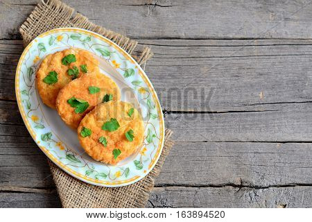 Fried vegetarian cutlets on a plate and on a wooden background with copy space for text. Delicious cutlets cooked with boiled dried peas, eggs, flour and spices. Diet food idea. Closeup. Top view