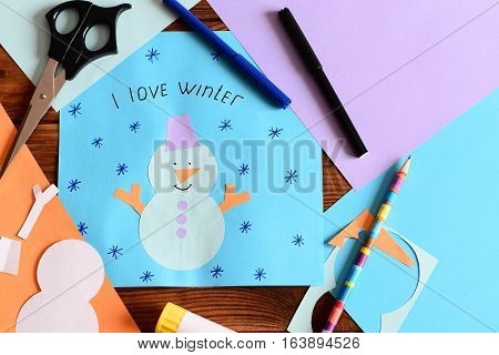 Snowman paper card with snowflakes and words I love winter. Materials for children winter crafts. Craft for development children fine motor skills and artistic taste, learning to use scissors and glue