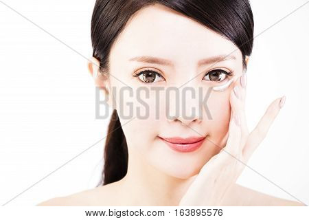 young woman applying skin cream under eyes