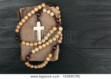 rosary and prayer book on a dark background