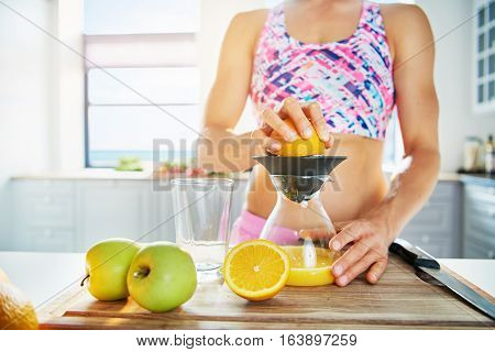 Sportive Woman Pressing Orange Juice With Squeezer